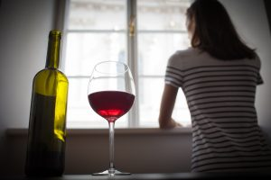 Woman drinking wine alone in a dark room