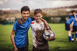 Teenage boys looking at the camera smiling after their soccer game. Both covered in mud.